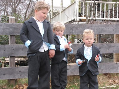 three boys in new Easter suits, posing by the fence