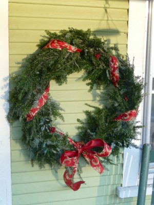 a hemlock wreath with red ribbon hanging by our front door