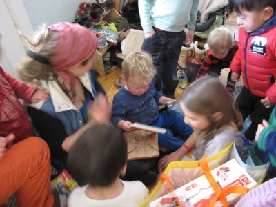 lots of kids crowding round as Lijah opens a present