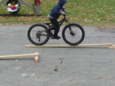 Zion riding his bike up a 2x4 ramp