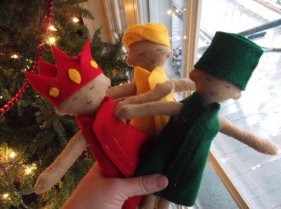 the three felt kings held in front of the Christmas tree