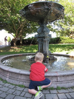Lijah kneeling by a fountain to put his hands in