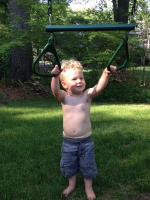 Lijah holding on to the rings/bar on a neighbor's play structure (feet firmly on the ground)