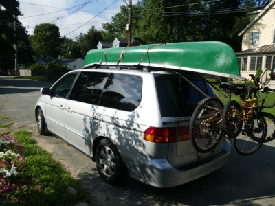 our van ready to go with canoe on top and bikes on back
