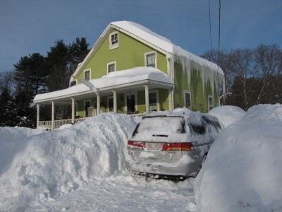 our house with lots of snow in front of it and lots of icicles on the eves