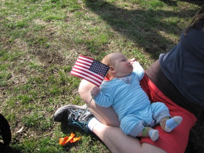 Elijah lying in Leah's lap holding an American flag