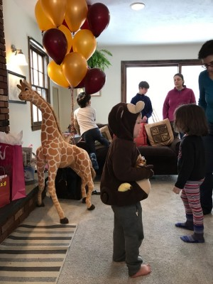 Lijah in a monkey costume standing near a giant stuffed giraffe at a birthday party