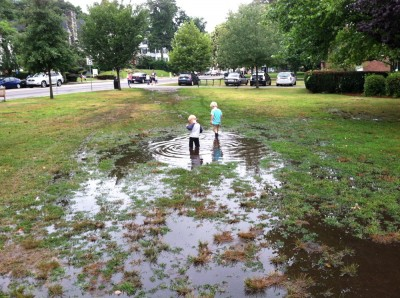 Zion and Lijah walking through a big puddle