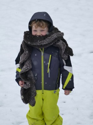 Lijah in the snow in his snowsuit, wearing a big scarf