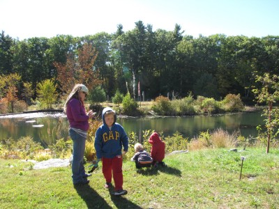 the family checking out art on the banks of the Old Frog Pond