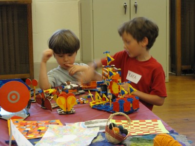 two boys playing with lego art together