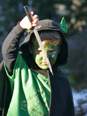 Lijah with green face paint, goblin ears, black cloak, and knife
