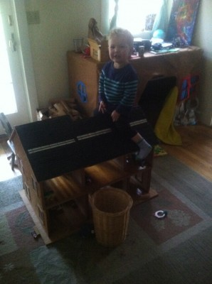 Lijah sitting astride a giant dollhouse in our playroom