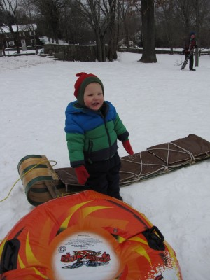Lijah standing happily with the sleds
