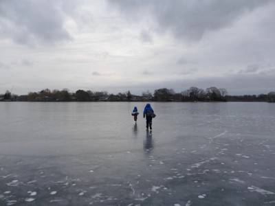 Zion and Harvey running on the dark ice of Spy Pond