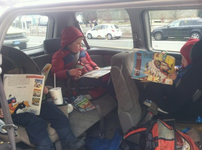 three boys reading three comic books in three car seats