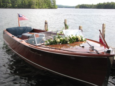 a Chriscraft runabout decorated with flowers at the dock