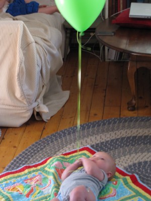 Elijah, on the ground, holding onto the string of a green helium balloon