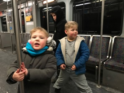 the boys standing up in an empty subway car