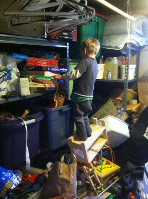 Zion standing on a precarious pile of junk, reaching for a toy in the messy basement