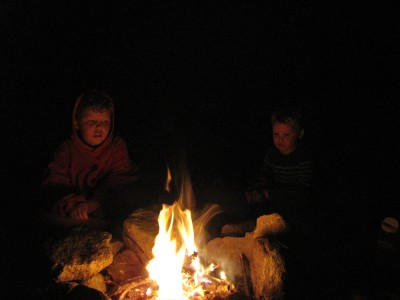 Harvey and Lijah sitting by the fire in the dark