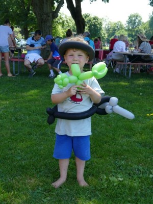 Lijah with a balloon hat, sword-belt, and pet