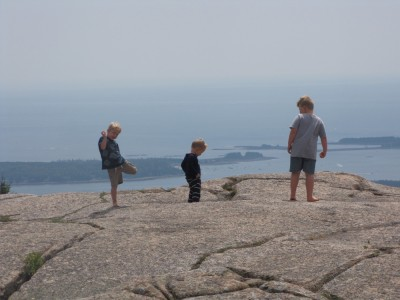 three boys barefoot atop a mountain