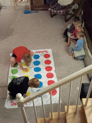 Harvey and Nathan playing Twister, the other kids manning the spinner