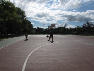 Harvey dribbling a basketball on an empty court, Lijah watching