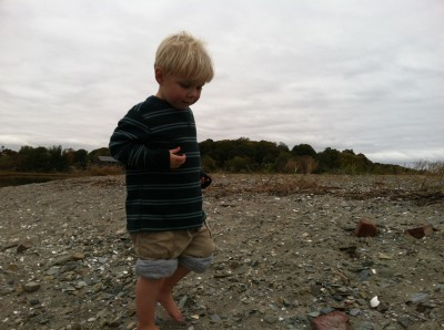Zion, barefoot with rolled-up pants, walking on the gravel beach