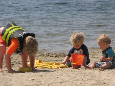 the three boys digging in the sand with water behind them
