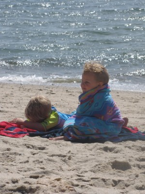 Zion lying on the beach, Lijah sitting wrapped in a  towel