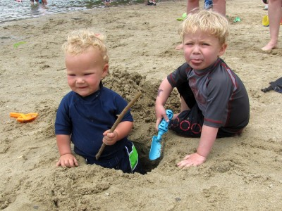 Zion and Lijah and the hole we dug; Zion spitting out sand