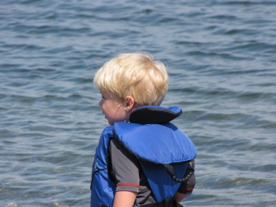 Zion in his life jacket by the water