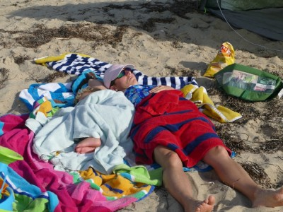 Mama and Lijah napping on the beach in a nest of towels