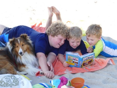 Zion reading a book to his brothers on the beach
