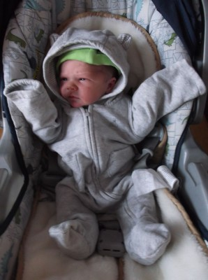 Elijah in the carseat wearing a hooded oversuit