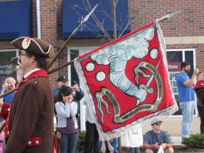 A Bedford minuteman carrying the town flag in the parade