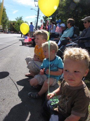 the boys with balloons waiting for the parade on the curb