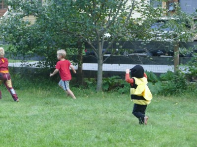 Lijah in a bee costume running after Zion in the yard