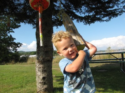 Lijah tugging on lobster bouys hanging from a tree