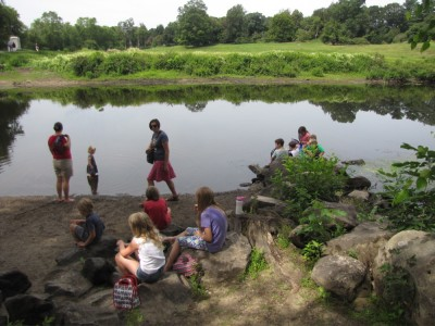 lots of kids picnicing on the shores of the Concord River