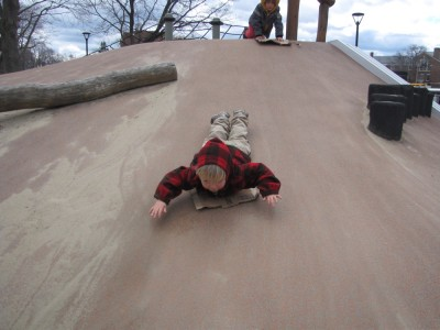 Zion sliding down a sandy concrete slope head first on a piece of cardboard
