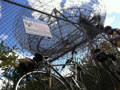my bike leaning against the fence in front of the Millstone Hill Steerable Antenna; with Luke and warning sign