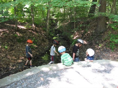 kids wading in a stream with bike helmets on
