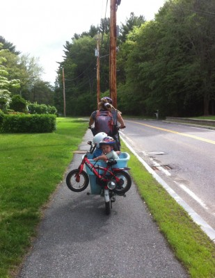 Leah riding the blue bike carrying Lijah and Zion; Zion's bike strapped on the back