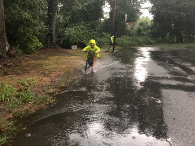 Zion riding his bike through a big puddle in the rain