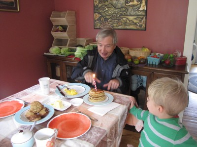 Grandpa and a stack of pancakes with a candle stuck in them