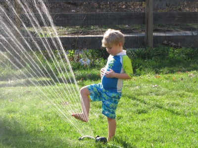 Zion playing in the sprinkler