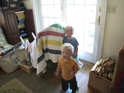 Zion and Elijah standing outside their house made from a blanket draped over the tipped-over rocking chair
